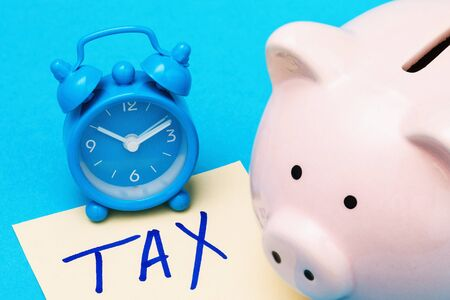 Piggy bank, alarm clock and sheet of paper on a blue background. Concept on the topic: time to collect money for taxes
