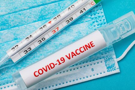 COVID-19 new coronavirus vaccine, thermometer and medical mask