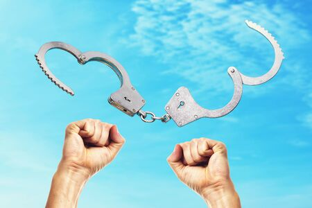 Open handcuffs and hands raised up amid the blue sky. Concept on the price of freedom