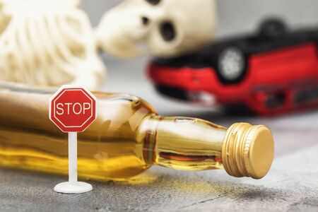 Road sign, a bottle of whiskey, a skeleton and an inverted car. Concept on the topic of drunk driver Reklamní fotografie