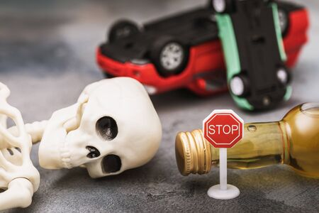 A road sign, a bottle of whiskey, a skeleton and an inverted car. The concept of drunken driving