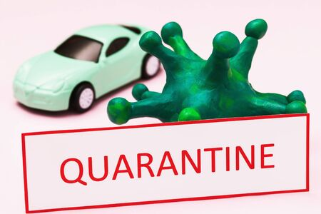 Tag with text, toy car and coronavirus, closeup. Concept on the ban on the movement of cars due to the outbreak of the COVID-19 pandemic