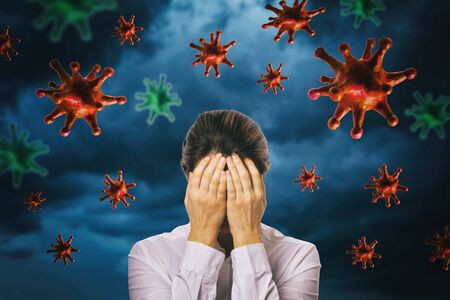 The girl closed her face with her hands against the background of a thunderstorm sky with a coronavirus. The concept of fear of the pandemic COVID-19