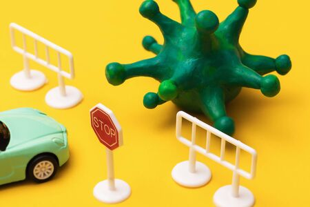 Toy road sign, car and coronavirus on a yellow background. Concept of travel ban due to covid-19 pandemic Banco de Imagens