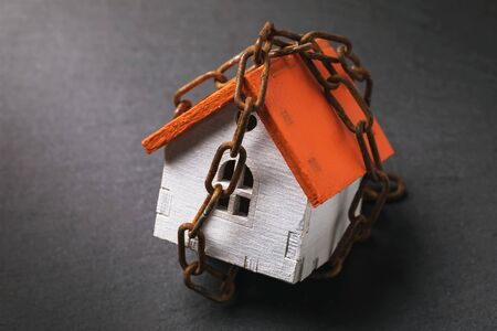 A toy house wrapped in a chain on a dark background. The concept of the arrest of property for tax evasion