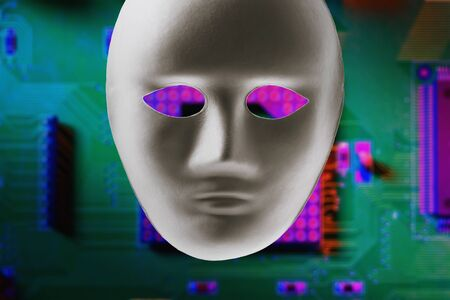 Paper mask on the background of a computer motherboard. Concept on the topic of anonymous hacking of computer systems