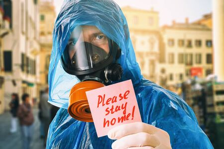 A man in a gas mask holds a note with the text. Concept to stay home because of the covid-19 pandemic Stock Photo