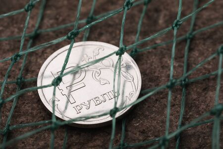 One Russian ruble is covered with a net. Currency Threat Concept Foto de archivo