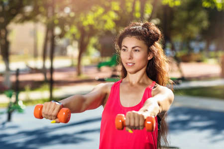 Girl exercises with dumbbells outdoors in a warm sunny morning. Concept on healthy lifestyle Reklamní fotografie