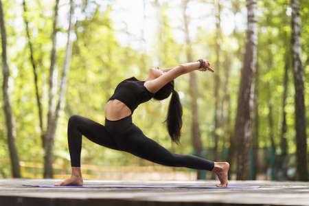 Female trainer in a summer sunny morning in sportswear, standing barefoot on a carpet, practicing yoga asana, performs the exercise of a warrior