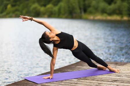A girl on a wooden bridge near the river, practices yoga asanas, performing the pose of a sage Reklamní fotografie