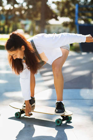 The girl learns to keep balance on the skateboard