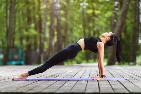 Female trainer in sportswear, practicing yoga asanas, doing the reverse plank