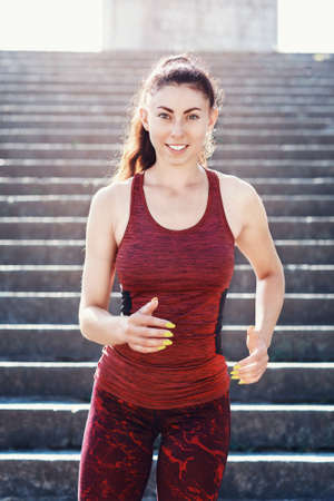 Girl athlete runs down the stairs on a sunny summer morning. Healthy lifestyle concept
