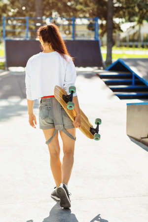Girl goes to ride a longboard on a sunny morning in a skate park