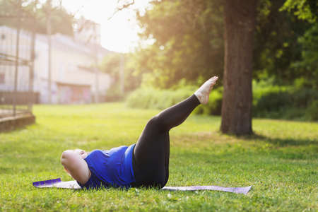 Young blonde size plus performs exercises for abdominal muscles in the park. The concept of a healthy lifestyle