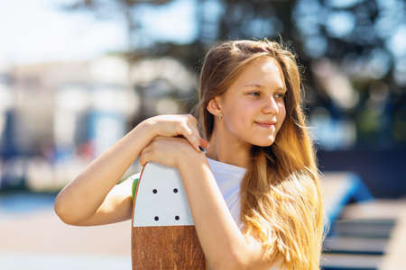 Portrait of a teenage girl holding a skateboard in her hands on a summer sunny day Stockfoto