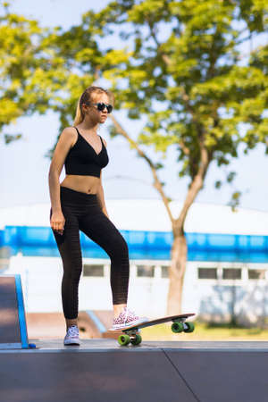 A teenager girl is preparing to move down from the springboard on a skateboard in the park Stockfoto