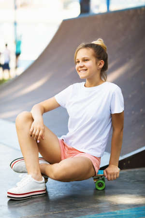 Satisfied teen girl resting on a skateboard while riding in the park Stockfoto