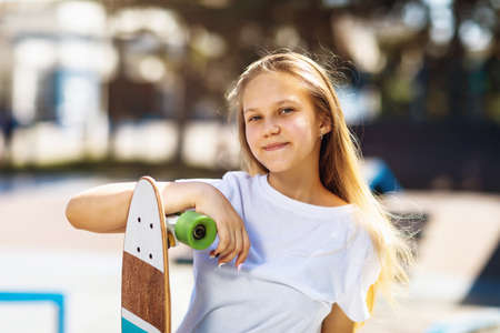 Girl teenager posing with a skateboard in her hands in the park on a summer sunny day