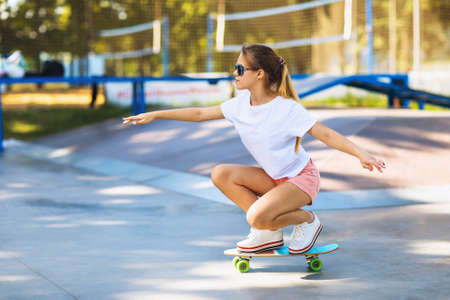 Girl teenager learns to keep balance on a skateboard in the park