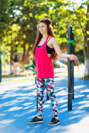 Girl athlete performs an exercise with a skipping rope on the playground on a warm sunny morning Stockfoto