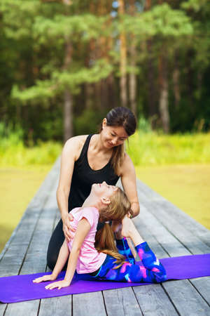 Mom and daughter perform gymnastic exercises on a sunny summer morning in the park. Concept on the topic of a healthy lifestyle