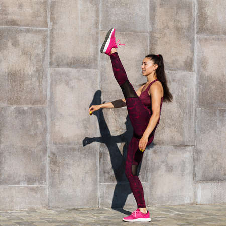 Girl athlete performs a warm-up before training on the street near the wall. The concept on the topic of sports and a healthy lifestyle. Stock fotó