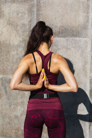 Girl athlete in a summer morning performs a stretching exercise, joining her hands behind her back. The concept of a healthy lifestyle and sports