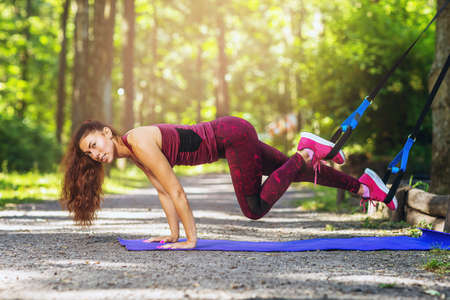 Brown-haired woman with long hair in a tracksuit doing exercises in the park using a suspension trainer Stock fotó