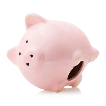 A pink piggy bank lies on its side, isolated on a white background