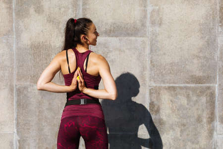 A young woman in sportswear performs a stretching exercise with her hands joined behind her back near the wall.