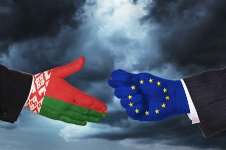 Hands on the background of a stormy sky. Concept on the topic of a proposal for friendship and difficult relations between Belarus and the European Union