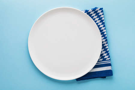 White ceramic plate with a Bavarian napkin on a blue background, top view. Food background