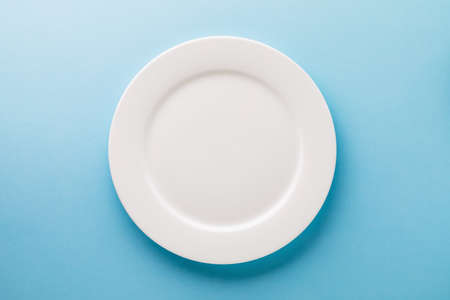 Flat ceramic plate white on a blue background, top view. Food background