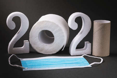 Medical mask and numbers made of foam and toilet paper in the shape of 2021.