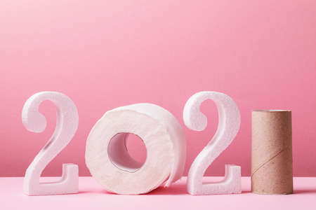 Toilet paper numbers in 2021 shape with copy space on pink background. A joke for the new year.