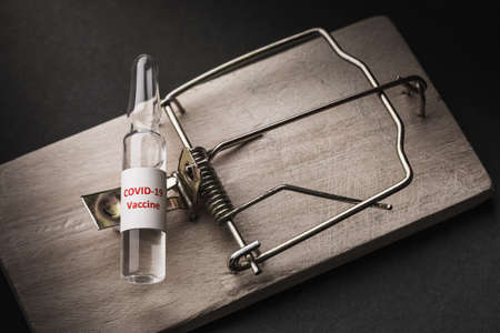 Ampoule with a vaccine against coronavirus in a mousetrap. Concept on the topic of drug counterfeiting.
