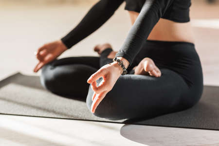 A woman in black sportswear practicing yoga, is engaged in meditation in the lotus position and performs the chin mudra symbol with her hands, close-up.