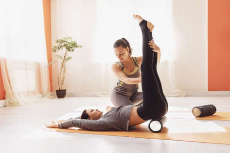 Myofascial release, the trainer shows the student the correct work with the sacrum and abs with the help of a massage roller.