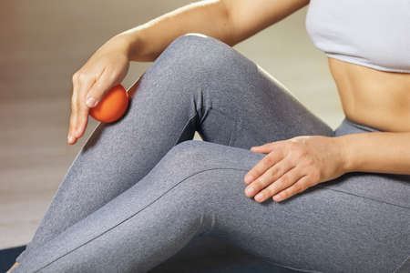 A woman performs myofascial release of the ankle muscles with a massage ball at home. The concept of preventing leg fatigue and self-massage.
