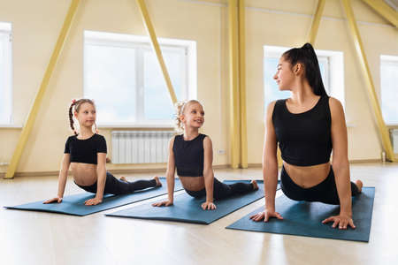 Woman trainer and two little girls practicing yoga in the studio are doing an exercise with a dog face up on gymnastic mats, Urdhva Mukha Shvanasana pose. Concept group training.
