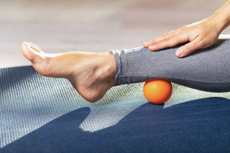 Myofascial relaxation of the leg muscles with a massage ball on a gymnastic mat at home. Prevent leg fatigue.