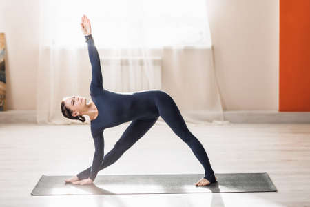 A beautiful middle-aged woman practicing yoga at home, doing extended triangle exercises, a trainer in dark blue sportswear stands in the Utthita Trikonasana pose on the mat.