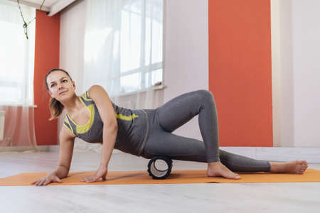 A woman in sportswear performs a myofascial massage of the thigh muscles with a roller on a mat in the room. Фото со стока