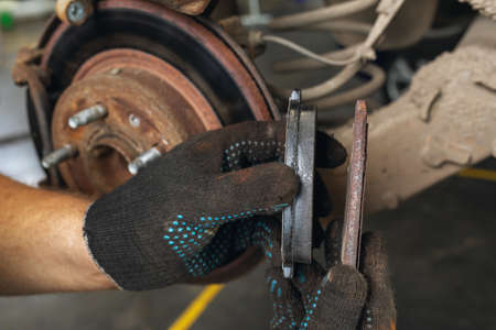 An auto mechanic shows the degree of wear of an old brake pad compared to a new one against the background of a car brake disc Banque d'images