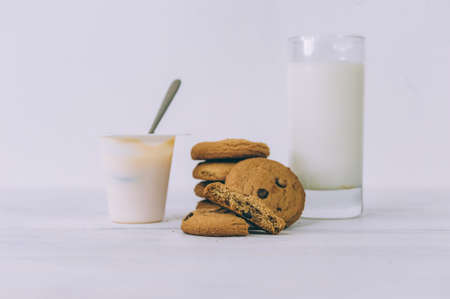 Oatmeal cookies with chocolate on a light background with a glass of milk and yogurt 스톡 콘텐츠