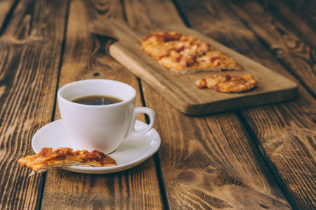 Little pizza on a wooden table with a cup of coffee. Fast food cooked at home 스톡 콘텐츠