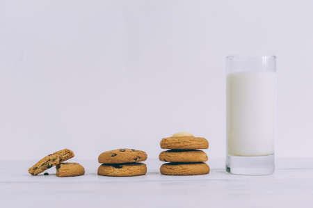 Oatmeal cookies with chocolate on a light background with a glass of milk