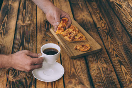 The guy holds pizza on a wooden table against the background of a cup of coffee. Fast food cooked at home 스톡 콘텐츠